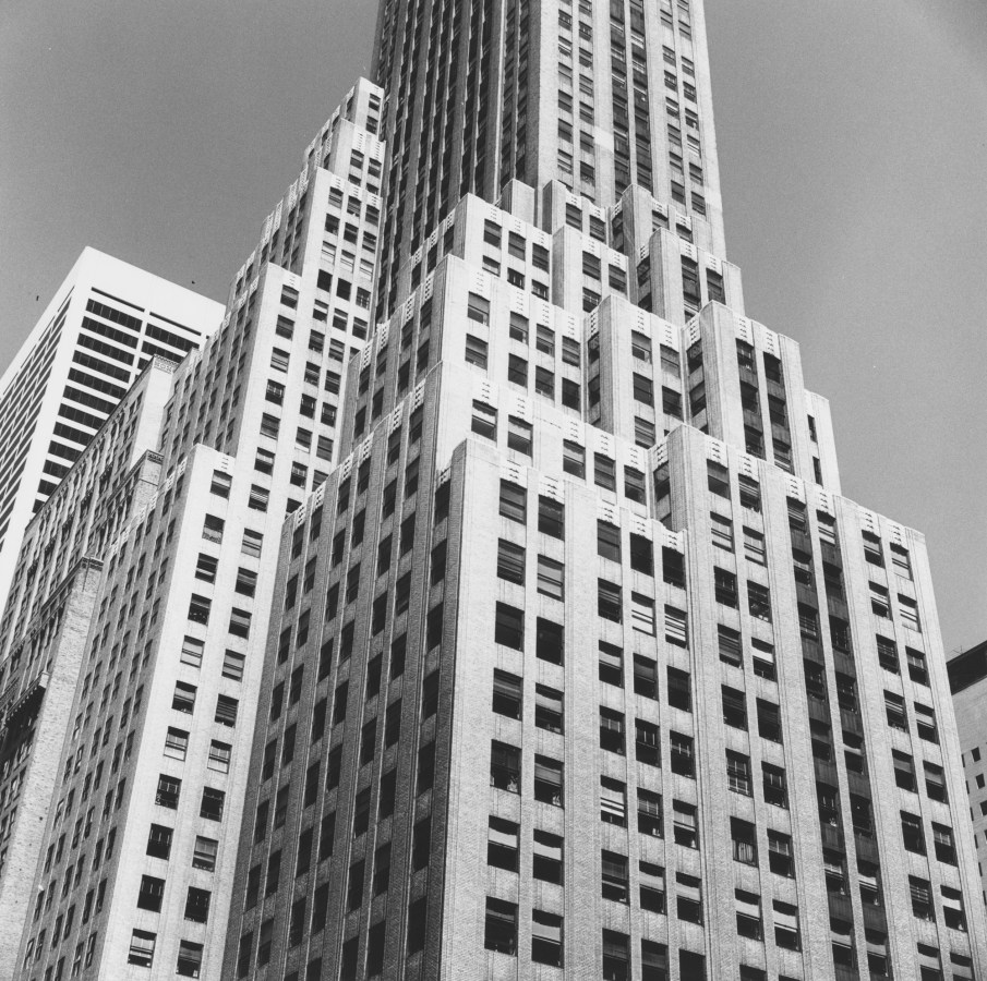 Black-and-white photograph of a stepped high-rise building from below