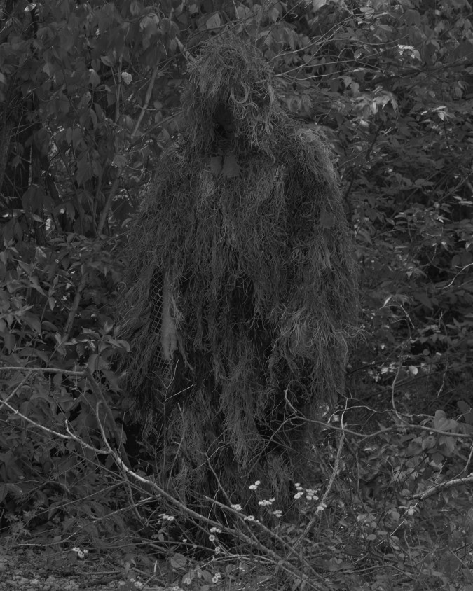 Black-and-white photographic portrait of a person in a moss-like camouflage costume against forest underbrush