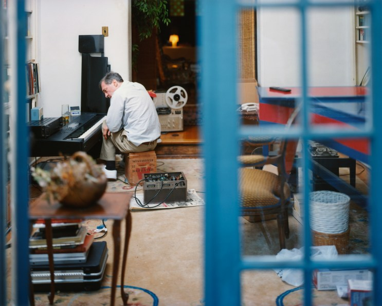Color photograph of a man seated at a piano keyboard through an open blue French door