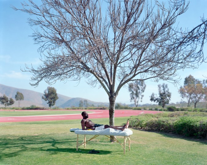 Color photograph of a man reclining on a massage table under a bare tree on a green lawn next to a running track