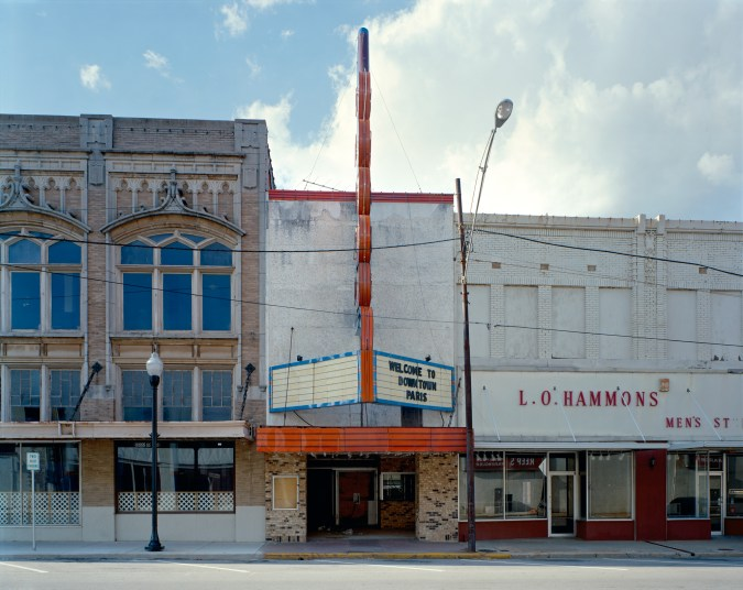 Color photograph of a movie theater with an oversized neon sign wedged between two other empty storefronts