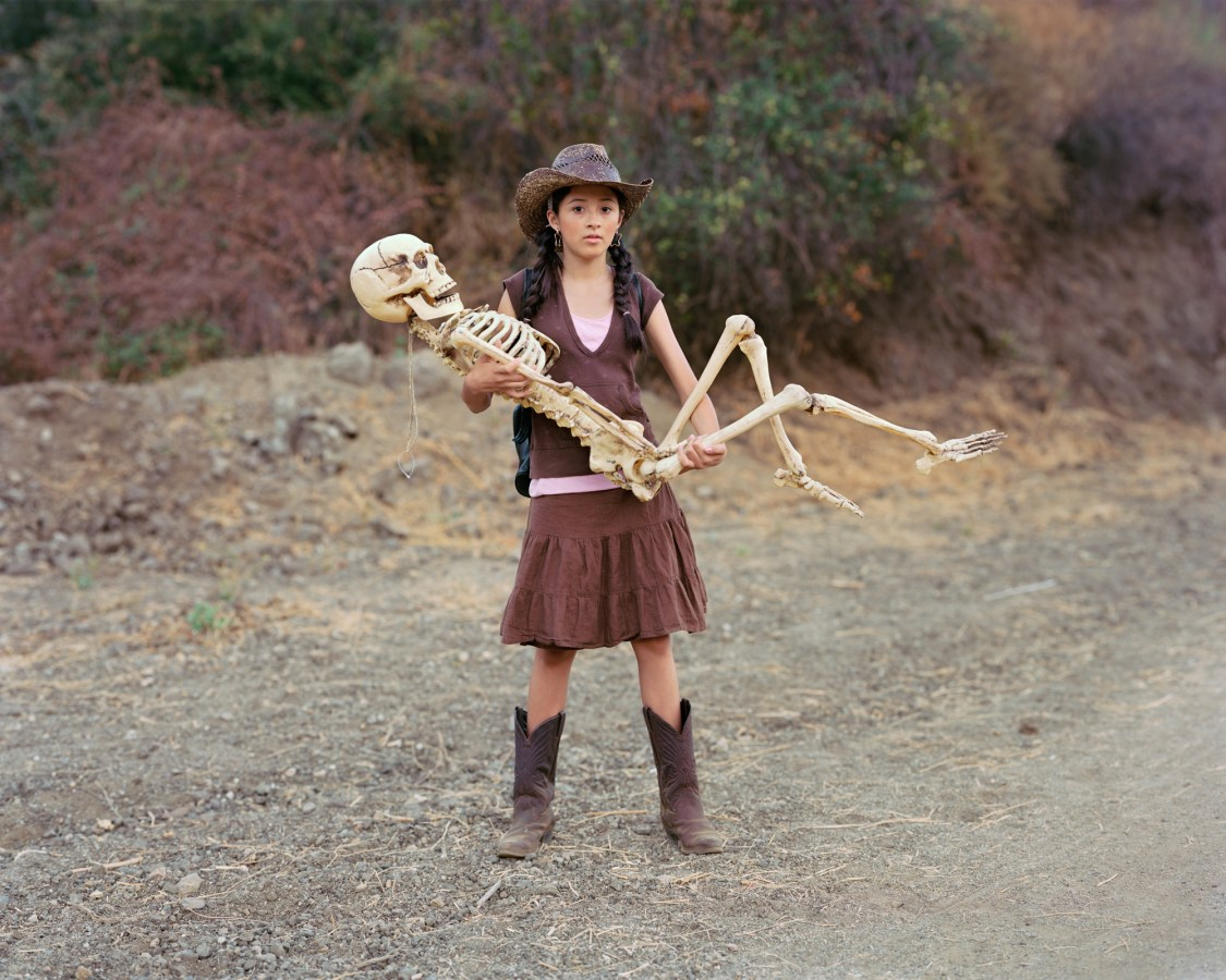 Color photograph of a girl in a cowboy hat and boots cradling a life-size plastic skeleton