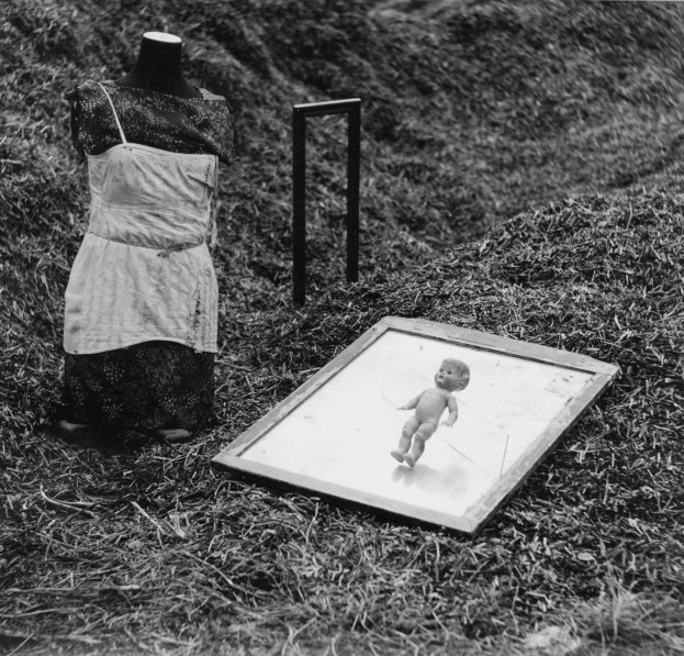 Black-and-white photograph of a headless mannequin positioned on the ground next to a small doll hovering above a tray