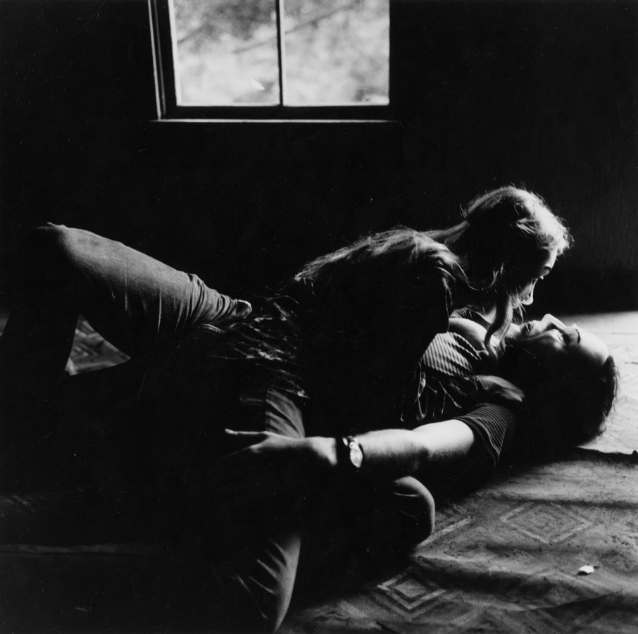 Black-and-white photograph of a couple in masks laying on the floor in embrace
