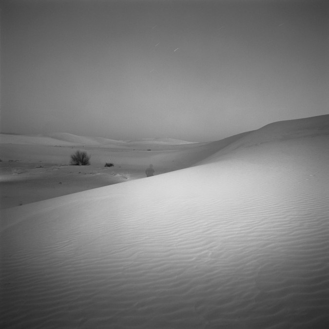 Black-and-white square photograph at night of a single figure amid a valley of sand dunes
