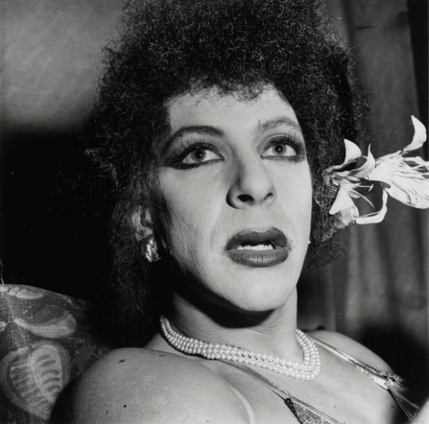 Black-and-white photograph of a person with curly hair, lipstick, and pearl necklace with a lily flower tucked behind one ear