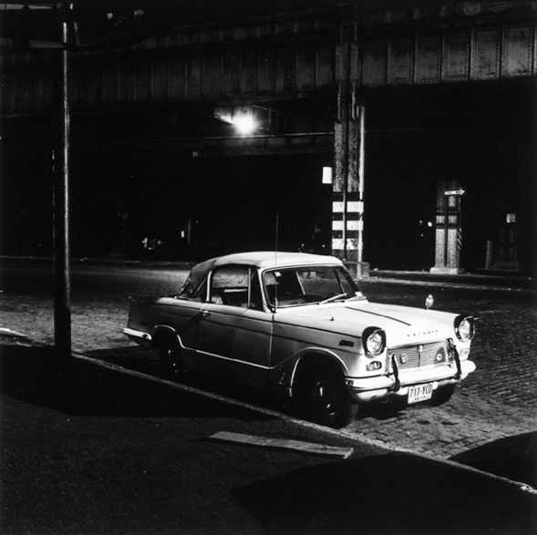 Black-and-white photograph of a small care parked on a cobbled street below an overpass