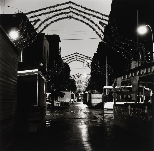 Black-and-white photograph of an empty street with marquees and tinsel arches spanning the road