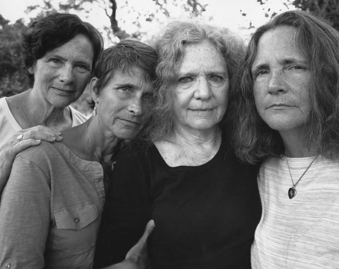 Black-and-white photograph of four women standing close, all looking at the camera.