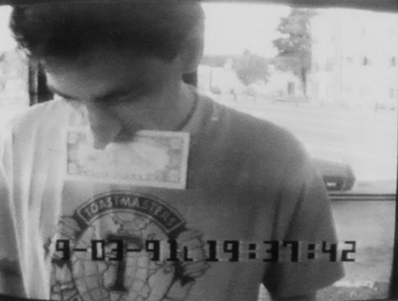 Black-and-white surveillance photograph showing a man holding money in his mouth at an ATM