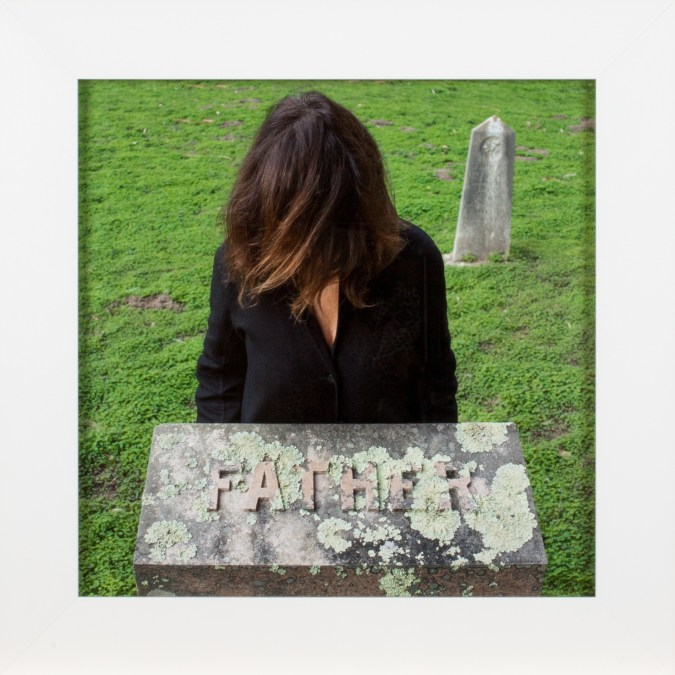 """A framed square photograph of a woman in a graveyard, behind a tombstone reading """"Father,"""" with her hair in front of her faace"""