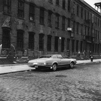 Black-and-white photograph of a car on an empty sttreet