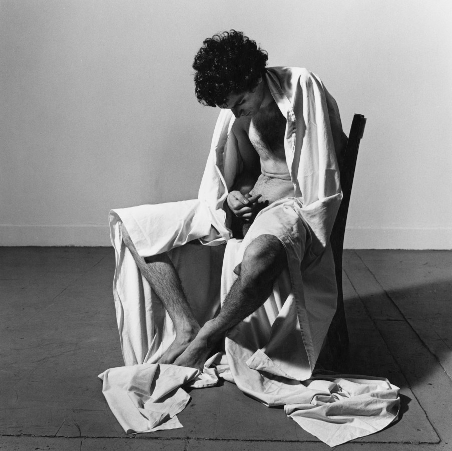 Black-and-white photograph of a nude man seated on a chair, draped in a sheet