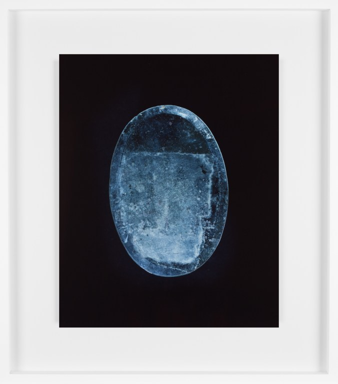 Color photograph of an oval blueish mirror with dust and streaks