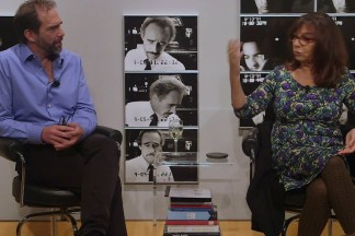 Video still of two people seated in front of a wall of photographs during a panel discussion