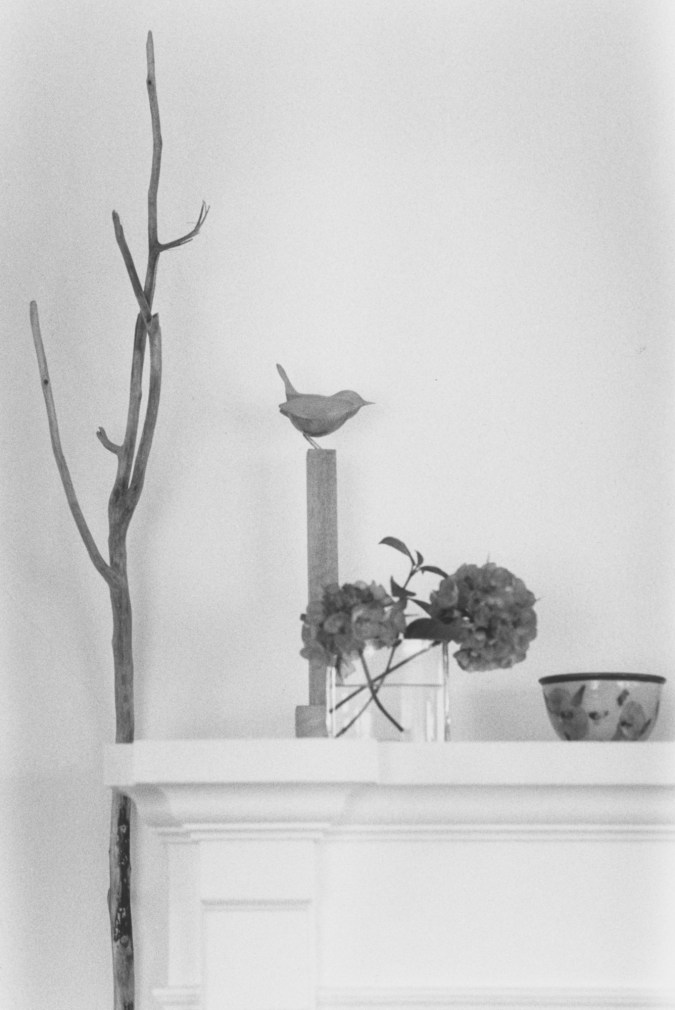 Black-and-white photograph of a mantle with carved wooden objects
