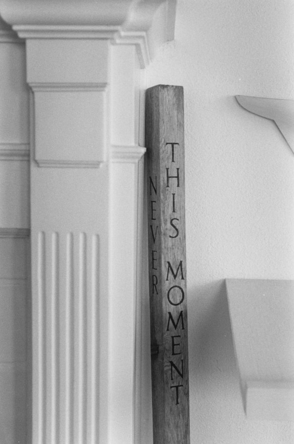 """Black-and-white photograph of a column and an engraved wooden staff which reads """"This Moment"""""""