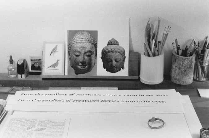 Black-and-white photograph of a tabletop with calligraphy writing, brushes, and postcards of Buddha head sculptures.