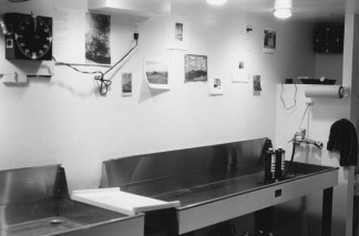 Black-and-white horizontal photograph of a photographic processing darkroom.