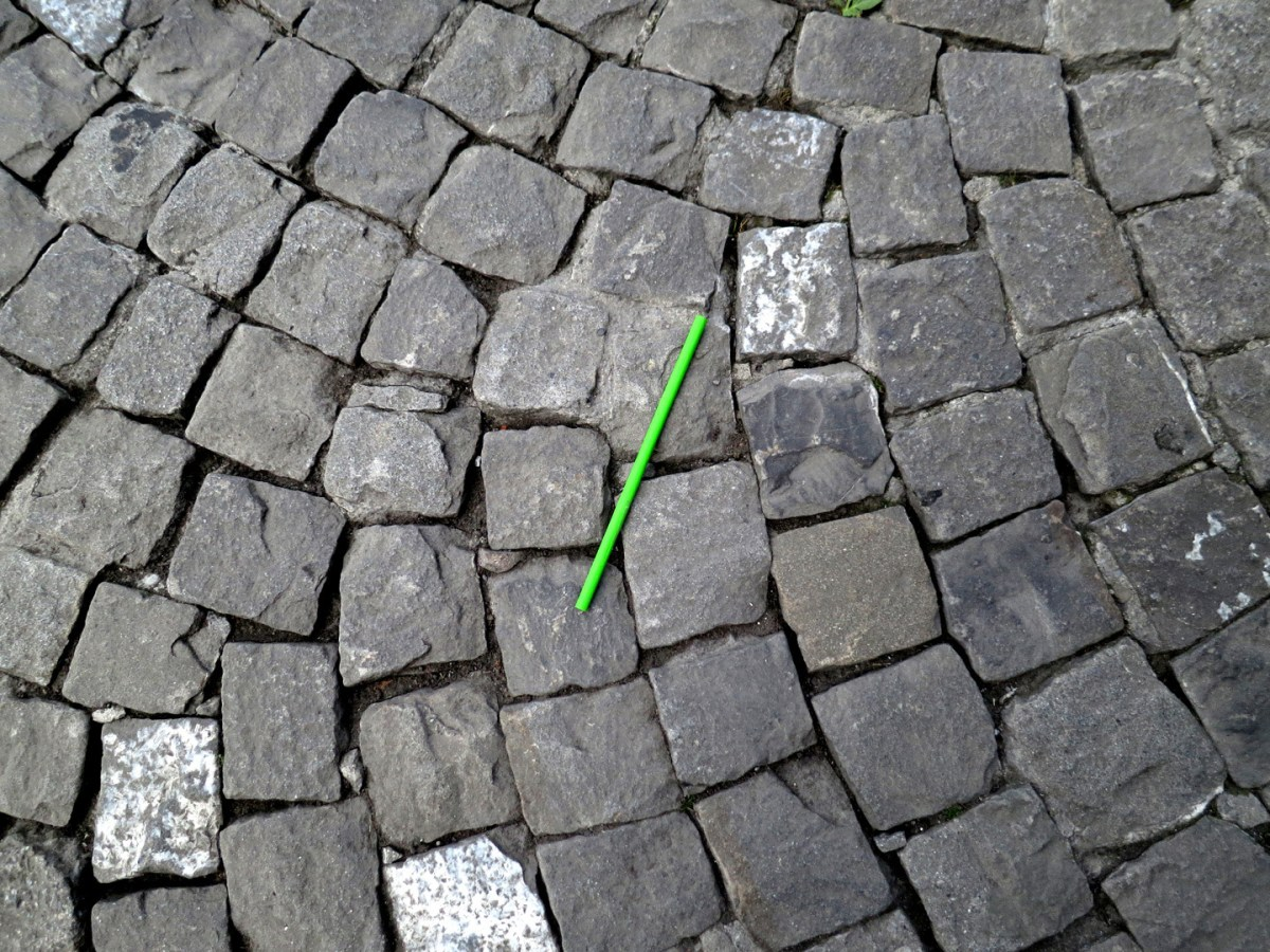 A photograph of a disposable green plastic straw on a cobblestone street
