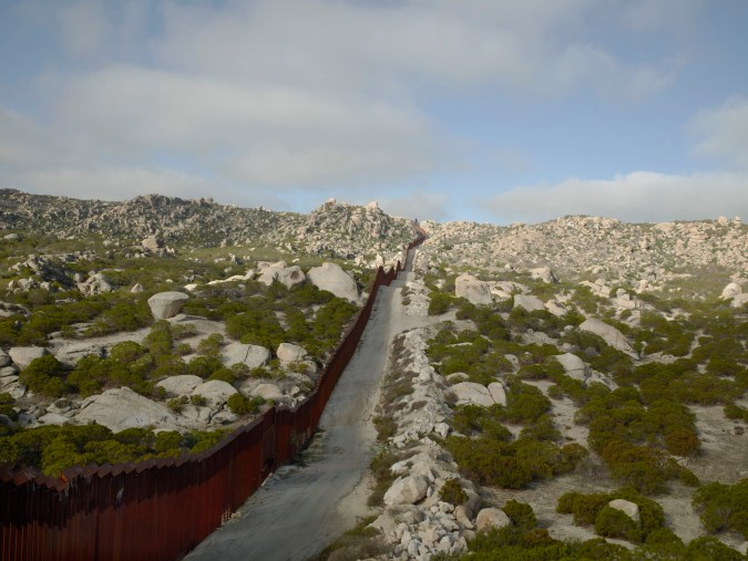 Color photograph of a metal fence running over a landscape of rocky hills and low green bushes into the horizon