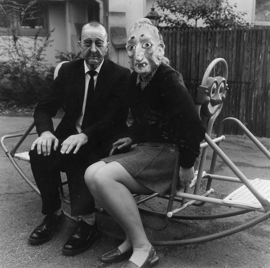 Black-and-white photograph of two people in Halloween masks seated on a see saw.