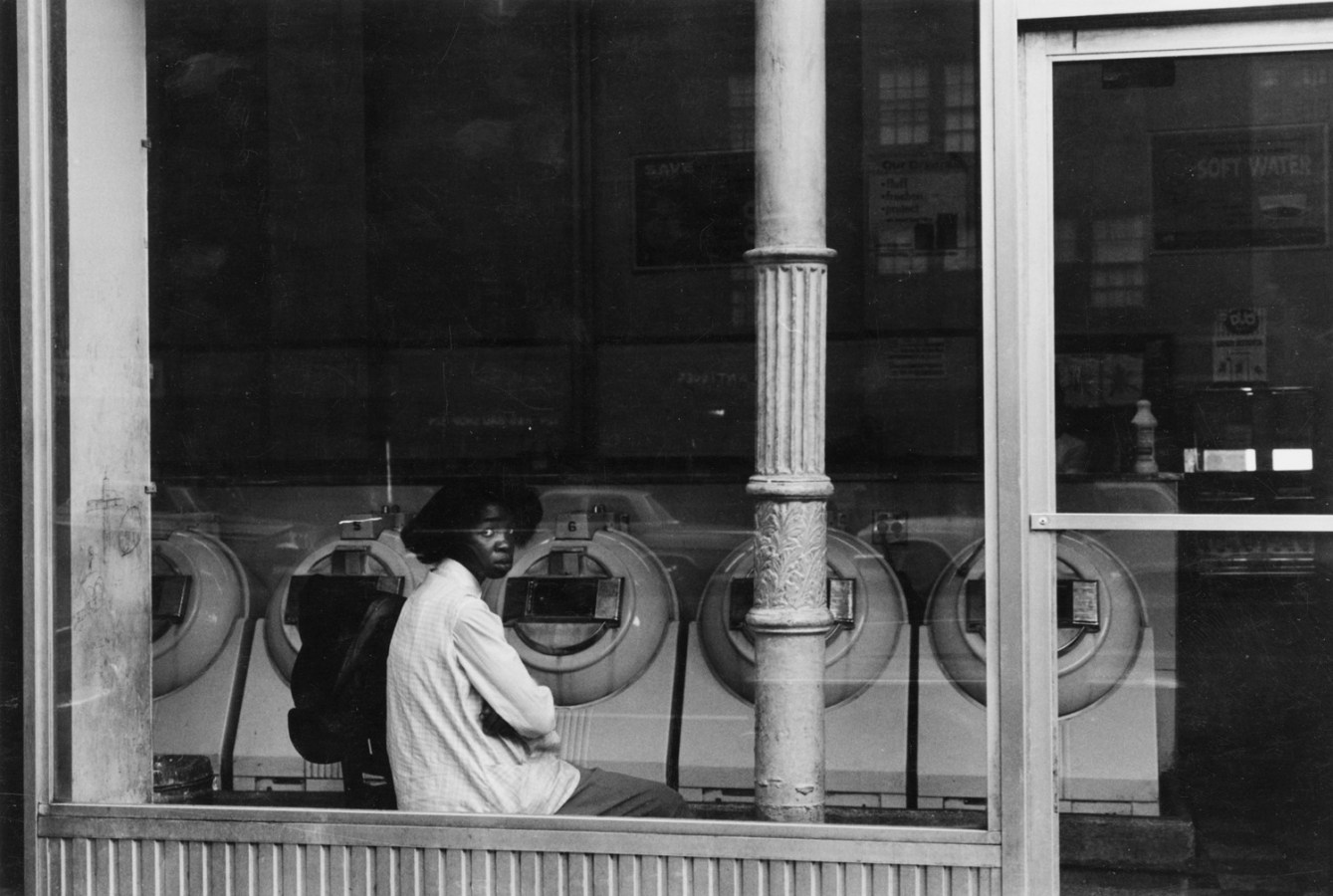 Black-and-white photograph of an African American woman seated in the window of a laundromat.