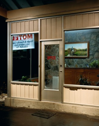 Color photograph of the outside of a motel lobby at night.