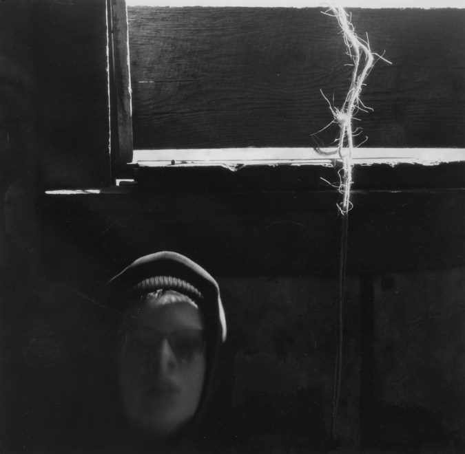 Black-and-white photograph of a person's slightly out-of-focus and shadowed face beneath a strand of twine coming through a window