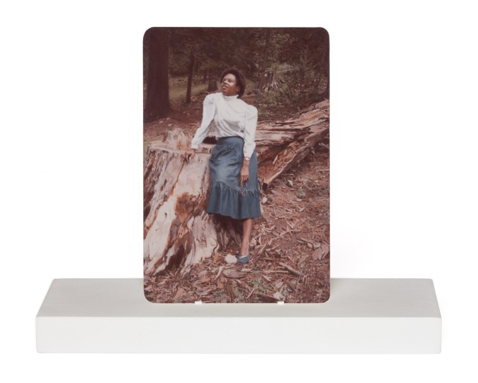 Painting of a woman leaning against a fallen tree on a wooden stand