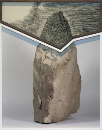 A framed etching of a mountaintop resting on top of a framed photograph of a rock in the same shape