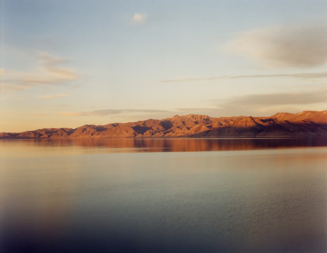 Color photograph of a low mountain range reflected in still water at sunset