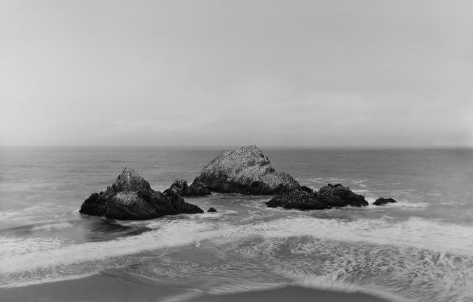 Black-and-white horizontal photograph of a rock formation in the Pacific Ocean.