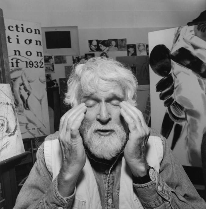 Black-and-white photograph of a man rubbing his eyes with paintings in the background