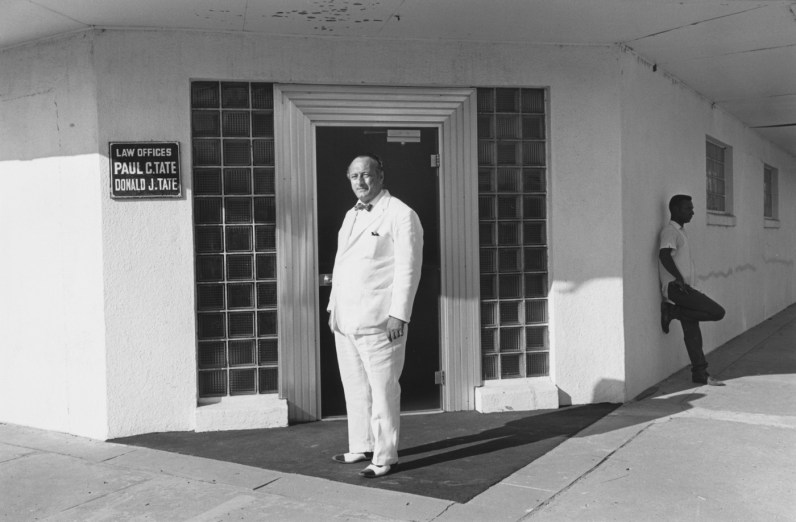 Black-and-white photograph of a man in a white suit standing in front of a doorway and another man to his right in the background