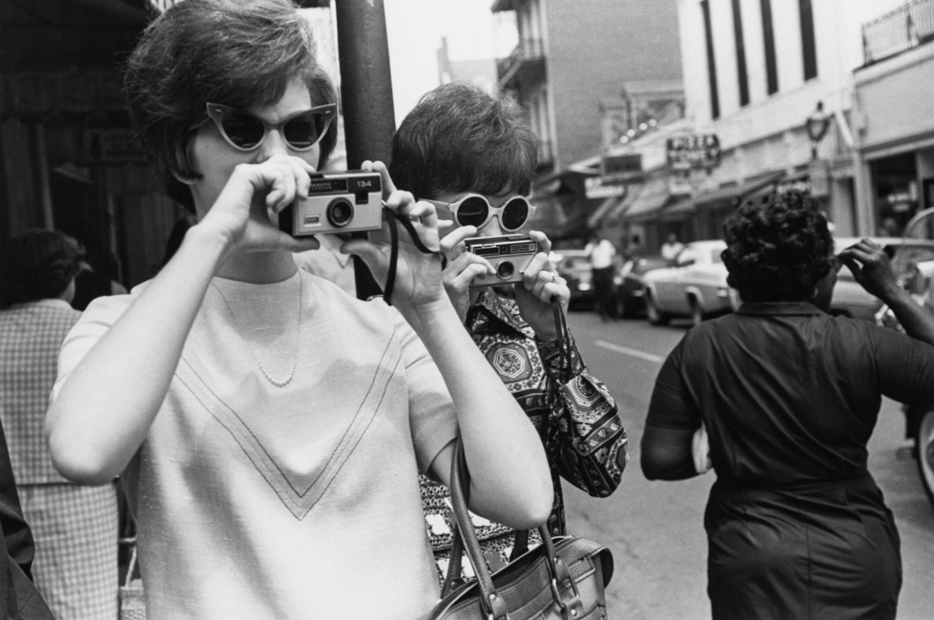 Black-and-white photograph of two women taking photographs on a city street