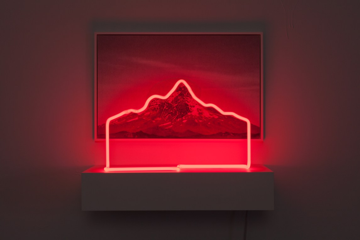 A red neon sculpture of a mountain silhouette in front of a photograph of the same mountain