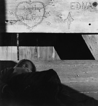 Black-and-white photograph of young boy with eyes closed; above him is a wood beam with various incised inscriptions.