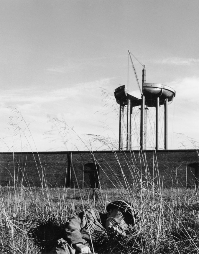 Black-and-white photograph of young boy in fringed jacket laying down in tall grass, with a tall industrial structure in the distant background.