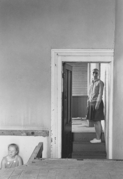 Black-and-white photograph of a woman in a mask standing in a doorway with a child in overalls on the lower left