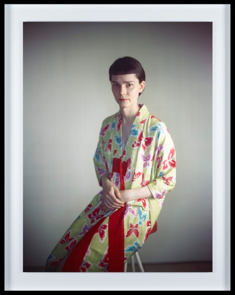 Color photographic portrait of a young woman with short hair and bangs dressed in a flower-patterned robe