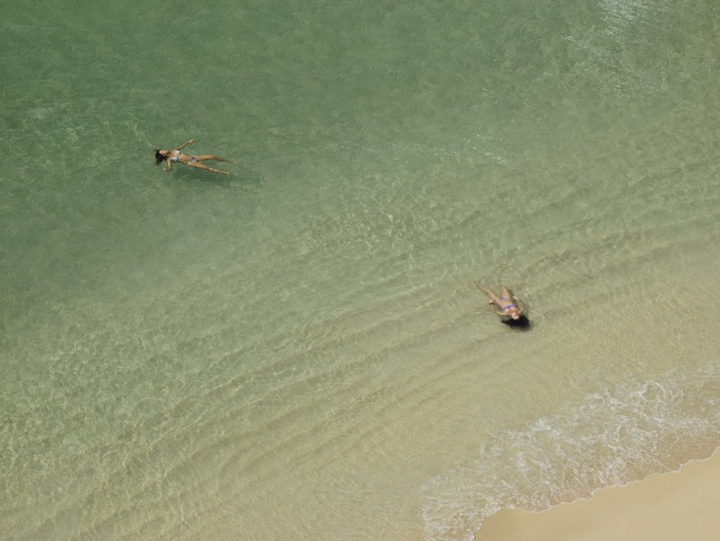 Color photograph of two women floating on the surface of a calm green sea near a sandy shore