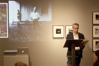Video still of a man standing at a podium in a gallery