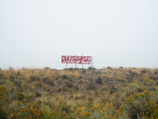 """Color photograph of an empty field with a hand-painted billboard reading """"Trump Loves American People"""""""