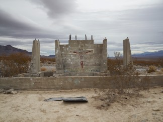 """Color photograph of old, abandoned house foundation riddled with shotgun shells, with grafitti painting of the crucifixion, captioned """"he will return"""""""