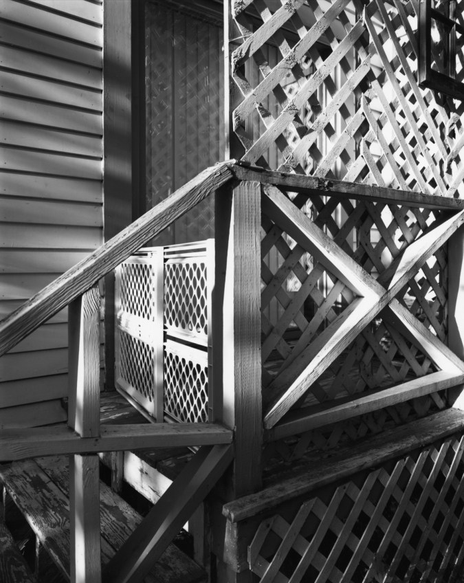 Black-and-white photograph of a latticed screen outside a window