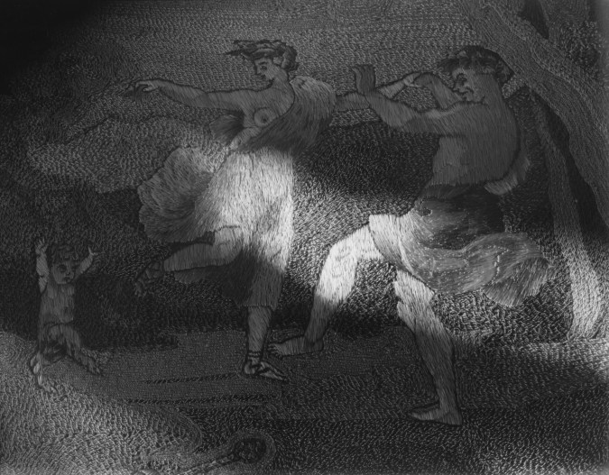 Black-and-white photograph of a patch of light on an embroidered picture of two dancing figures and a satyr