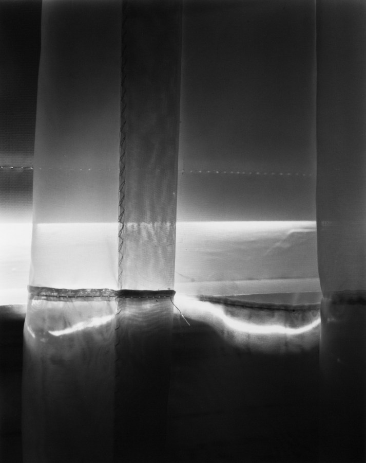 Black-and-white photograph of light and shadow through a curtain