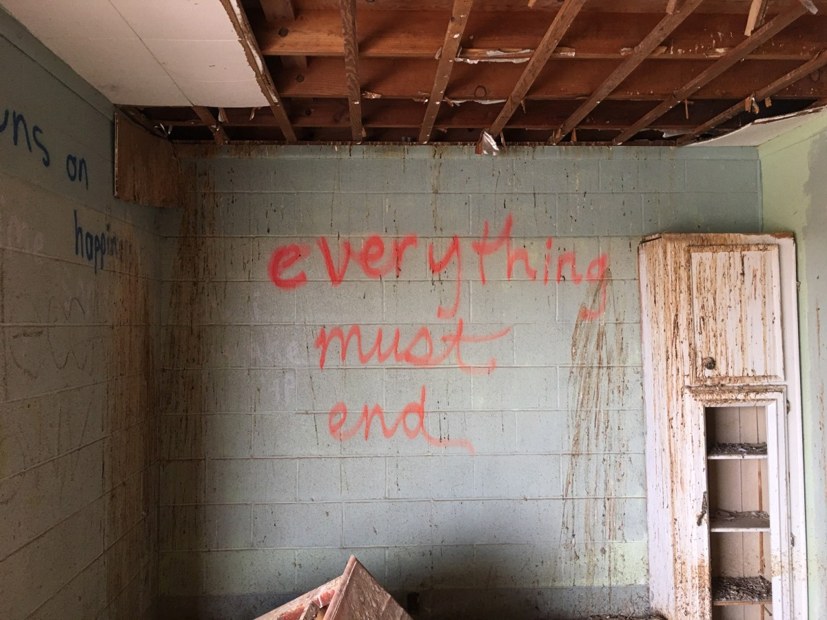 Color photograph of fluorescent red spray-painted writing on an interior cinderblock wall of an abandoned building