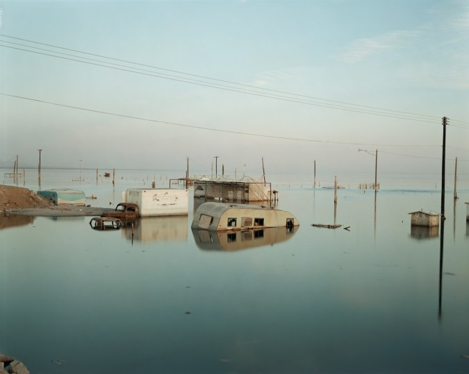 Color photograph of telephone poles, decrepit trailer homes, and vehicles partly submerged in still water
